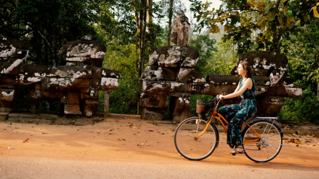 young caucasian woman riding  bicycle  in angkor wat - angkor stock videos and b-roll footage