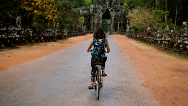 Young Caucasian woman riding  bicycle  in Angkor Wat