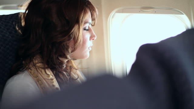 Young caucasian woman sitting on aeroplane