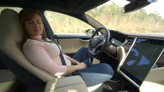young caucasian woman sleeping while her cool autonomous car drives. tired girl on a long road trip sleeps in the high tech self steering car. - car interior stock videos & royalty-free footage