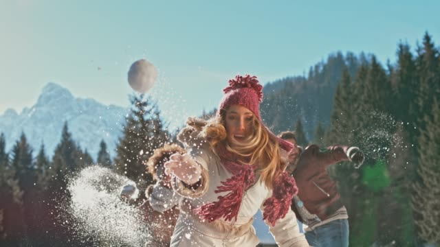 SLO MO Young Caucasian woman throwing a snowball into the camera