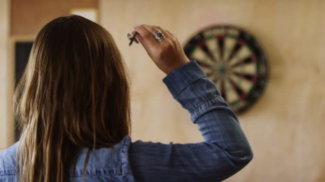 a young caucasian woman with a ring and long brown hair aims and throws darts at a dartboard - darts stock videos and b-roll footage