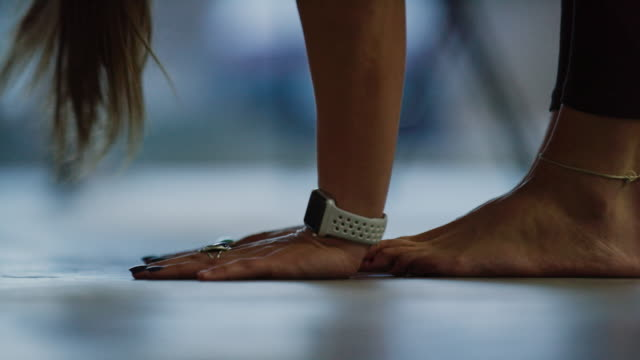 a young caucasian woman with a watch puts her hands on the floor in a forward bend and then stands up again in an exercise studio - ballet dancing stock videos & royalty-free footage