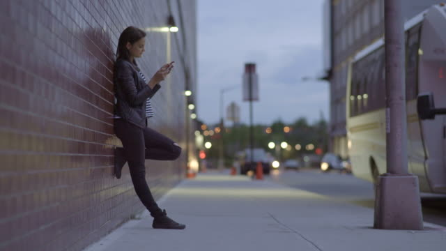 young caucasian women using tablet computer outdoors in the city