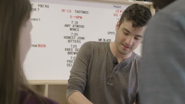 stockvideo's en b-roll-footage met a young caucasiuan store clerk works on an ipad then rings up a purchase of non-alcoholic bitters at a neighborhood market and wine shop. - financieel item