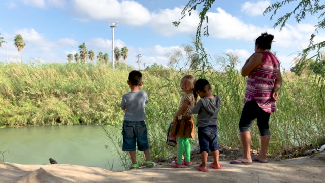 young central american asylum seekers stand on the bank of the rio grand at a camp for asylum seekers, as cameras from american surveillance tower... - mexican american stock videos & royalty-free footage