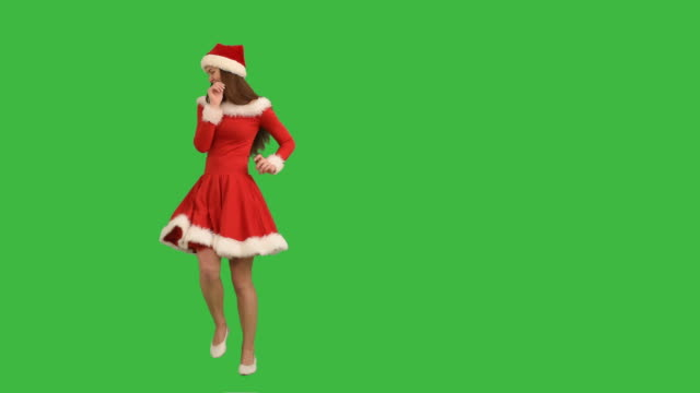 young charming girl in a red dress and  hat  santa claus plays the fool and invites himself to join  on a green background - santa hat stock videos & royalty-free footage