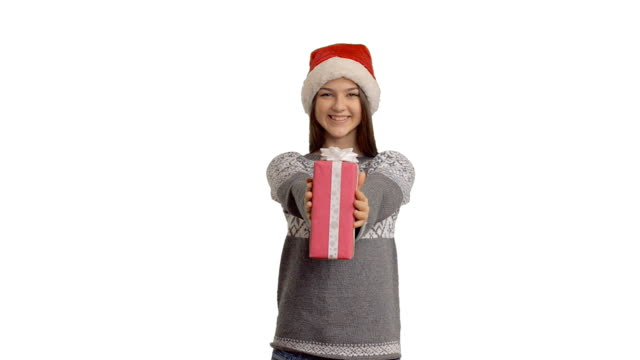 young charming girl presenting a gift in a santa claus hat - santa hat stock videos & royalty-free footage