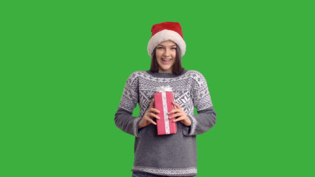 young charming girl presenting a gift in a santa claus - santa hat stock videos & royalty-free footage