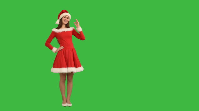 young charming girl showing an copy space  and shows okay in a red dress and  hat  santa claus on a green background - santa hat stock videos & royalty-free footage