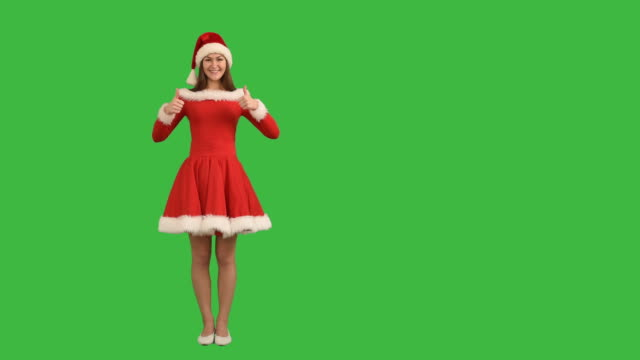 young charming girl showing an copy space  and shows thumb in a red dress and  hat  santa claus on a green background - santa hat stock videos & royalty-free footage
