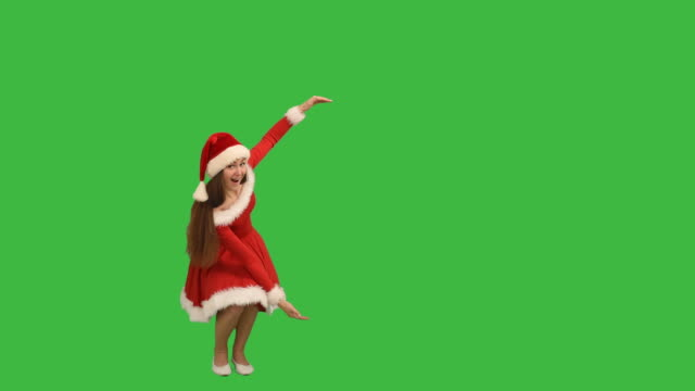 young charming girl showing an copy space  and smiling in a red dress and  hat  santa claus on a green background - santa hat stock videos & royalty-free footage