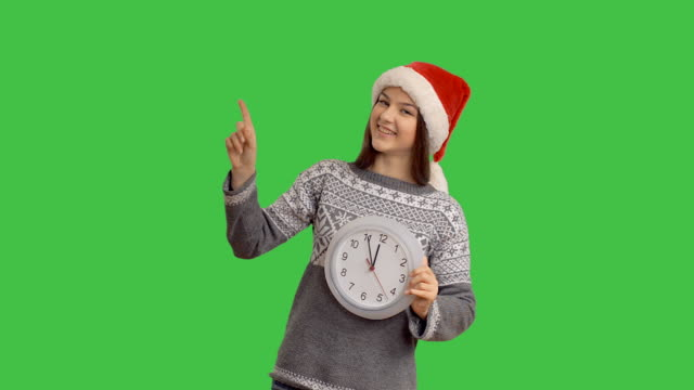 young charming girl showing on the clock hinting that soon the midnight showing cope space on green background - santa hat stock videos & royalty-free footage