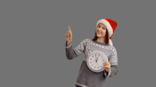 young charming girl showing on the clock hinting that soon the midnight showing cope space on gray background - santa hat stock videos & royalty-free footage