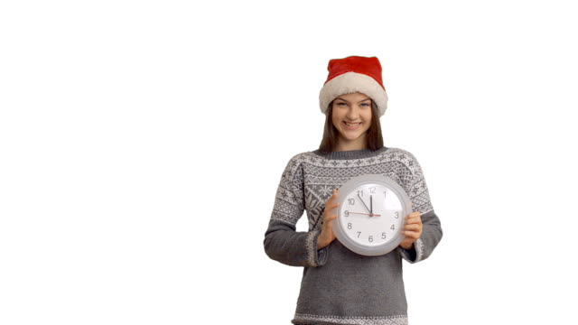 young charming girl showing on the clock hinting that soon the midnight showing cope space on white background - santa hat stock videos & royalty-free footage