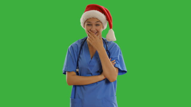 young charming nurse laughs on a green screen - santa hat stock videos & royalty-free footage
