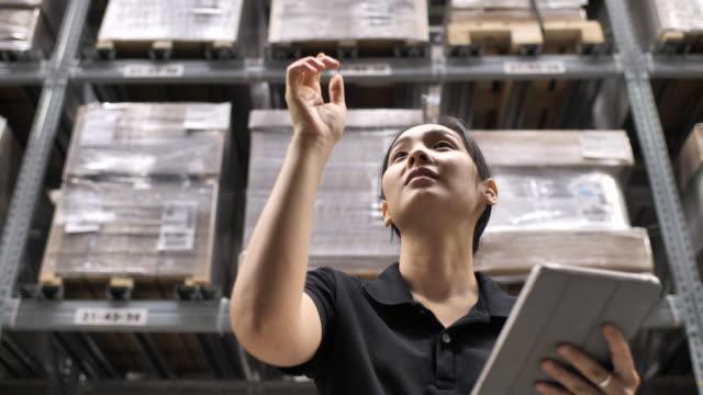若い陽気な女性労働者は工場ストレージ領域に彼女のタブレットを使用しています。 - 整理点の映像素材/bロール