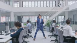 Young Cheerful Handsome Business Manager Wearing a Suit and Tie Dancing in the Office. Diverse and Motivated Business People Work on Computers in Modern Open Office.