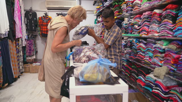 a young cheerful muslim man, a seller, is helping a european tourist, an active 50-years-old senior woman, to choose clothes in a small clothing retail store in sri lanka. - sri lankan culture stock videos & royalty-free footage