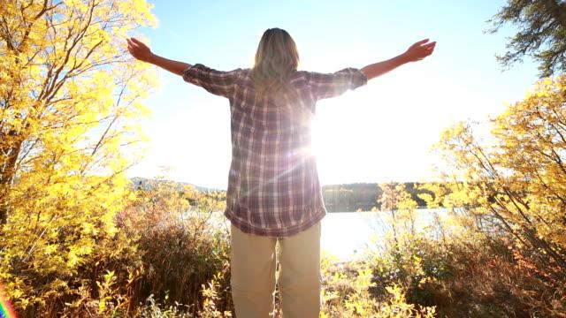 Ung glad kvinna armarna utsträckta i naturen