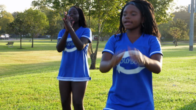 ms young cheerleaders clapping together while practicing routine during early morning workout in park - cheerleader stock videos and b-roll footage