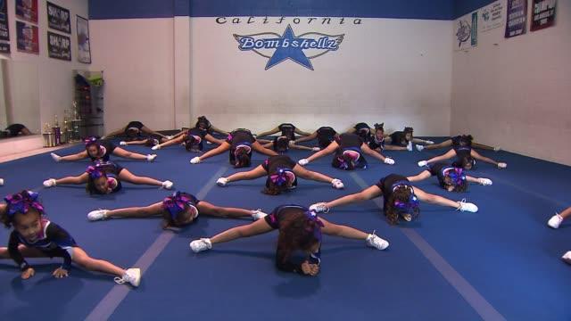 young cheerleaders do the splits - チアリーダー点の映像素材/bロール
