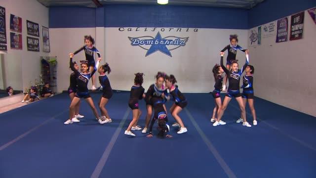 young cheerleaders perform stunts - チアリーダー点の映像素材/bロール