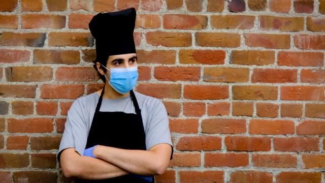 vídeos de stock, filmes e b-roll de jovem chef posando com uma máscara de proteção e luvas durante uma pausa olhando para longe - braços cruzados