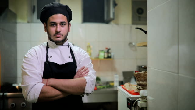 Young chef standing in kitchen alone