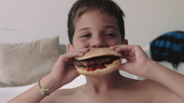 vídeos y material grabado en eventos de stock de young child boy eating hamburger - comida no saludable
