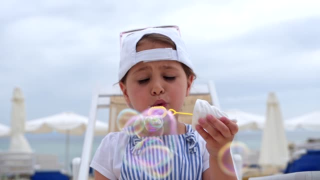 young child enjoying blowing bubbles with soap sud - soap sud video stock e b–roll