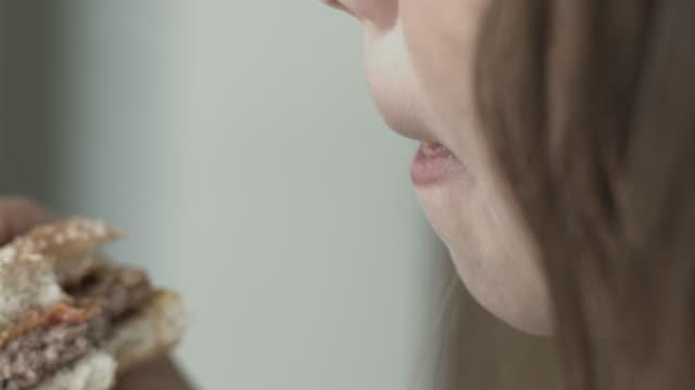 vídeos y material grabado en eventos de stock de young child girl eating hamburger - comida no saludable