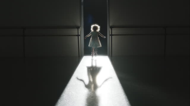 Young child in dress leaping towards camera backlit