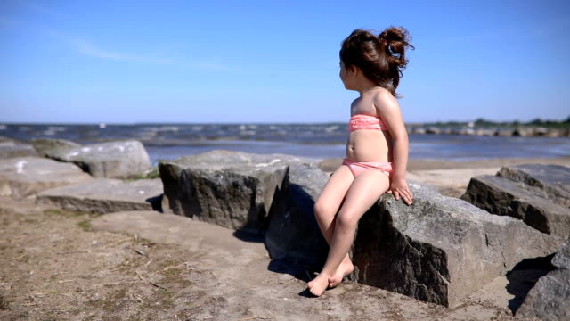 Young child sitting on a rock on a beach looking at the sea