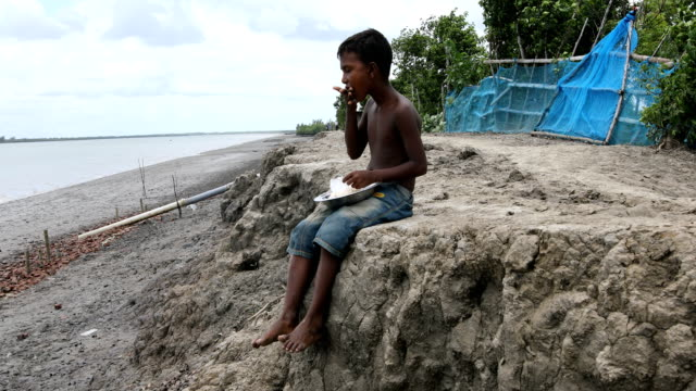 stockvideo's en b-roll-footage met young child taking food near bank of the river in the coastal area in bangladesh on august 17, 2020. a un report says, over 19 million children-a... - quarter
