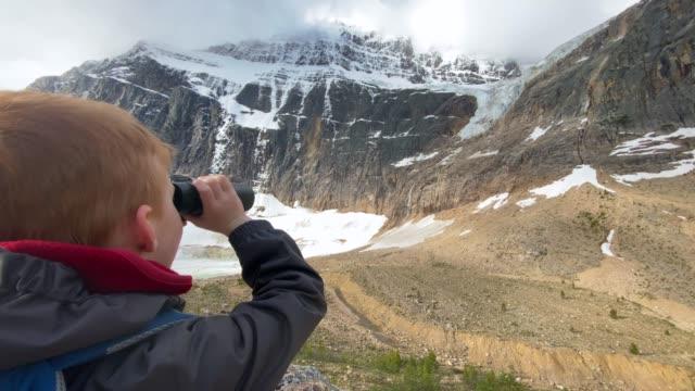 カナダ アルバータ州 ジャスパー、マウント エディス カヴェルで双眼鏡を使用した幼い子供 - ジャスパー国立公園点の映像素材/bロール