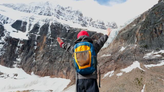 カナダ アルバータ州 ジャスパーマウント エディス カヴェルで腕を上げた幼い子供 - ジャスパー国立公園点の映像素材/bロール