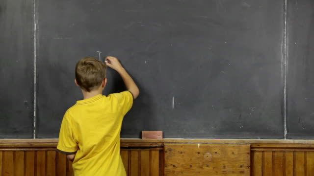 young child writes on blackboard in retro classroom - blackboard stock videos and b-roll footage