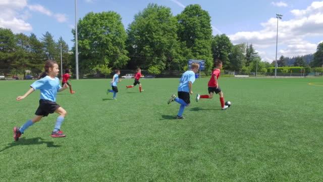 Dribbilng un balón de fútbol el campo durante un juego de niños