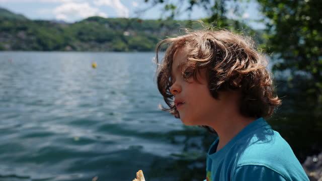 bambini che pranzano picnic in riva al lago - top capo di vestiario video stock e b–roll