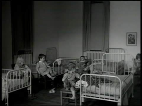 young children in dorm room taking off shoes preparing for bed institution orphans foundlings fostering - 1946 stock videos and b-roll footage