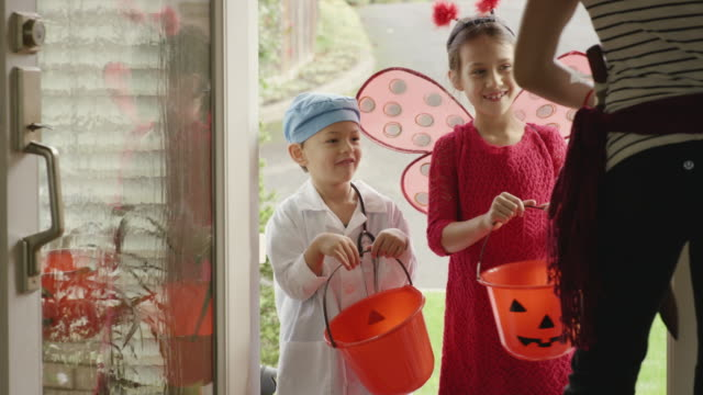 Young children knocking on door trick or treating on halloween