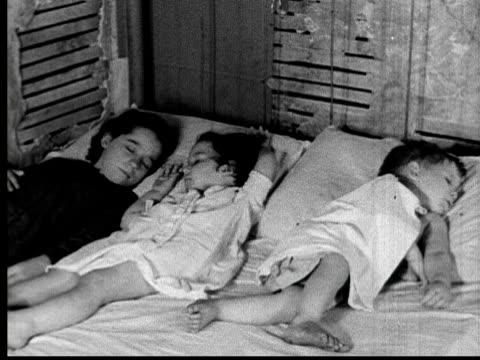 stockvideo's en b-roll-footage met 1935 ms 3 young children lying on bed sleeping in room with run down walls/ usa - grote depressie nieuwsevenement