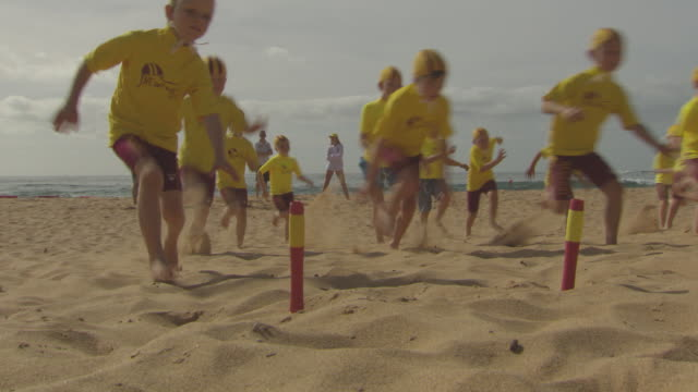 young children nippers line up laying face down on the sand then get up and run towards the finish tokens in the ground beach flag sprint race back... - bagnino video stock e b–roll