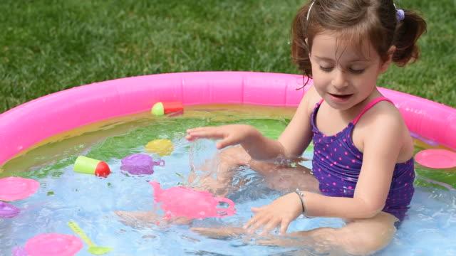 stockvideo's en b-roll-footage met jonge kinderen in het zwembad spelen en plezier - buitenbad