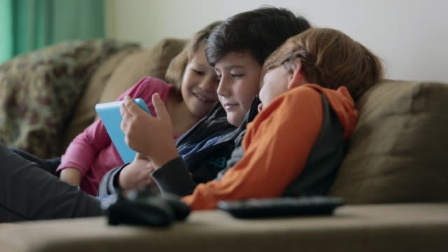 vídeos de stock, filmes e b-roll de ms young children sitting on sofa watching tablet device together, smiling - três pessoas