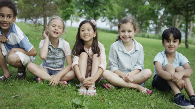 young children sitting together outdoors - nursery school building stock videos and b-roll footage