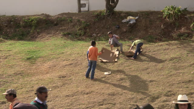 vídeos de stock e filmes b-roll de young children sliding down grassy hill on cardboard, one knocks another over, villa de leyva market, villa de leyva, boyacã¡ department, colombia - colômbia