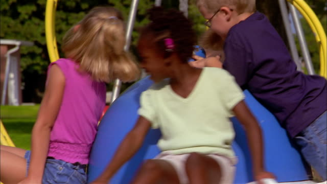 Young children spin on a merry-go-round.