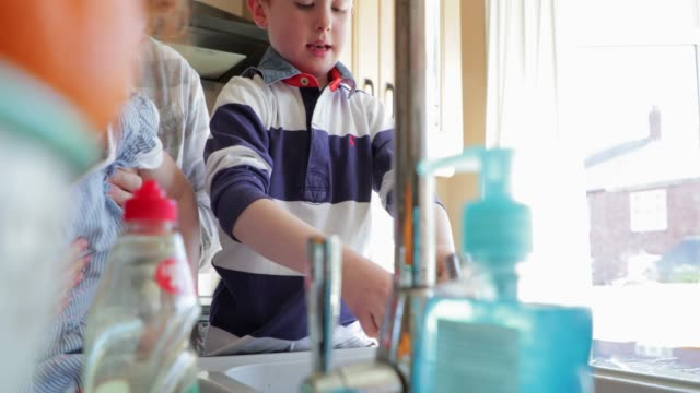 young children washing the dishes with mummy - washing up stock videos & royalty-free footage